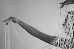 Stående av en ung attraktiv kvinna med avtäckta skuldror som drar dekorativt trådarna av en radgardin med händer royaltyfri fotografi