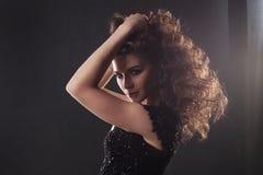 Stående av en ung attraktiv kvinna med ursnyggt lockigt hår attraktiv brunett arkivfoto