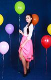 Stående av en ung attraktiv kvinna nära många ljusa ballonger Royaltyfria Bilder