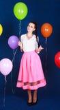 Stående av en ung attraktiv kvinna nära många ljusa ballonger Arkivfoto