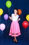 Stående av en ung attraktiv kvinna nära många ljusa ballonger Royaltyfri Bild