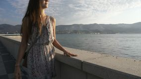 Stående av en ung attraktiv kvinna som går på stadssjösidan, steadicamskott lager videofilmer