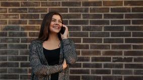Stående av en ung attraktiv kvinna som ler samtal på telefonen mot en tegelstenvägg på solnedgången lager videofilmer