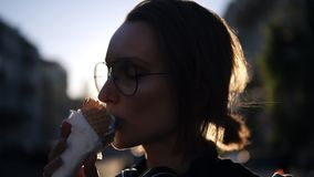 Stående av en ung blond flicka som slickar en glass i dillandekotte på gatan Sun shines on the background arkivfilmer