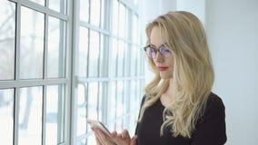 Stående av en ung blond kvinna i exponeringsglas med en telefon på det stora fönstret lager videofilmer