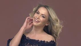 Stående av en ung blond kvinna i makeup lager videofilmer