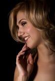 Stående av en ung blond kvinna med härligt krullande hår- och professionellsmink På en mörk bakgrund arkivbilder