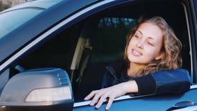 Stående av en ung caucasian kvinna i en bil Sitta i platsen för chaufför` s och att se kameran som ler stock video