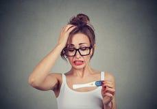 Stående av en ung chockad kvinna med graviditetstestet royaltyfri bild