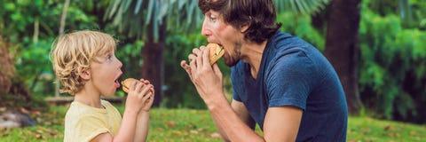 Stående av en ung fader och hans son som tycker om en hamburgare i en parkera och ler långt format för BANER royaltyfria foton