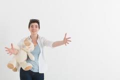 Stående av en ung flicka i den vita skjortan på den ljusa bakgrunden Se för le och fördjupningshänderna de kamera, Arkivfoton