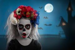Stående av en ung flicka i ett smink på en allhelgonaaftonkrans med röda blommor på hennes huvud royaltyfri fotografi
