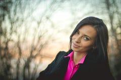 Stående av en ung flicka i höstskogen på solnedgången rosa skjorta royaltyfri fotografi