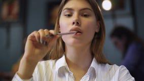 Stående av en ung flicka i en vit skjorta som sitter i ett kafé som rymmer en penna nära kanterna lager videofilmer
