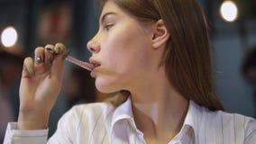 Stående av en ung flicka i en vit skjorta som sitter i ett kafé som rymmer en penna nära kanterna Flickan skriver därefter blicka lager videofilmer