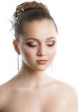Stående av en ung flicka med en bröllopmakeup Perfekt hud, slätt hår, stora crystal örhängen och hårprydnad Isolering på Royaltyfri Bild