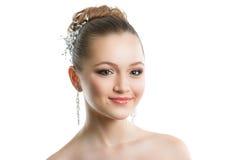 Stående av en ung flicka med en bröllopmakeup Perfekt hud, slätt hår, stora crystal örhängen och hårprydnad Isolering på Royaltyfria Foton