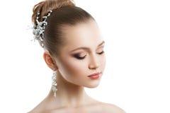 Stående av en ung flicka med en bröllopmakeup Perfekt hud, slätt hår, stora crystal örhängen och hårprydnad Isolering på Arkivfoto
