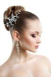 Stående av en ung flicka med en bröllopmakeup Perfekt hud, slätt hår, stora crystal örhängen och hårprydnad Isolering på Fotografering för Bildbyråer