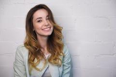 Stående av en ung flicka med krullning och ett öppet leende på en vit bakgrund arkivbilder