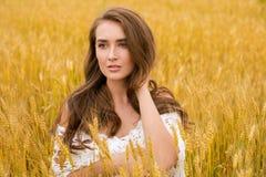 Stående av en ung flicka på en bakgrund av det guld- vetefältet royaltyfria bilder