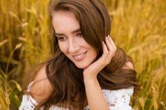 Stående av en ung flicka på en bakgrund av det guld- vetefältet arkivfoton