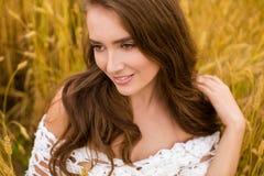 Stående av en ung flicka på en bakgrund av det guld- vetefältet arkivbilder
