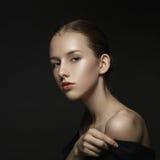 Stående av en ung flicka på en mörk bakgrund Fotografering för Bildbyråer