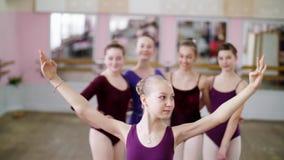 Stående av en ung flickabalettdansör i en lila balettbody, le som utför behagfullt ett balettdiagram arkivfilmer