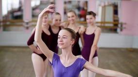 Stående av en ung flickabalettdansör i en lila balettbody, le som utför behagfullt ett balettdiagram lager videofilmer