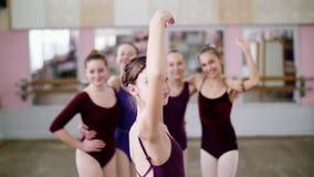 Stående av en ung flickabalettdansör i en lila balettbody, le som utför behagfullt ett balettdiagram stock video