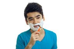 Stående av en ung grabb med skum på hans framsida som ler och rakar hans skäggmaskin Royaltyfri Fotografi