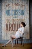 Stående av en ung gravid kvinna i den vita skjortan i fotostudio Arkivbild