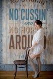 Stående av en ung gravid kvinna i den vita skjortan i fotostudio Fotografering för Bildbyråer