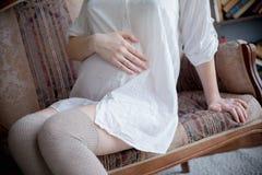 Stående av en ung gravid kvinna i den vita skjortan i fotostudio Arkivfoto