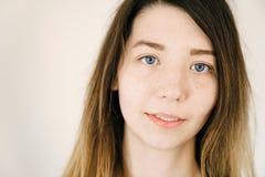 Stående av en ung gullig vit flicka med stora uttrycksfulla blåa ögon och kottar på en ljus bakgrund Arkivbild