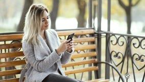 Stående av en ung härlig affärskvinna med en mobiltelefon i parkera arkivfilmer