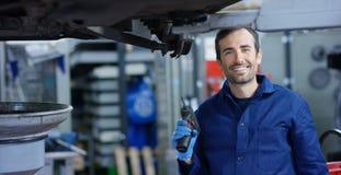 Stående av en ung härlig bilmekaniker i ett bilseminarium, i bakgrunden av en reparation för bilservicebegrepp av maskiner, fel arkivbild