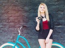 Stående av en ung härlig blond flicka i ett svart omslag och kortslutningar som poserar nära tegelstenväggen bredvid en ljus blå  Arkivfoto