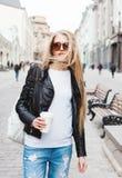 Stående av en ung härlig blond flicka med solglasögon som går på gatorna av Europa med kaffe Vinden som blåser hennes hairO royaltyfri fotografi
