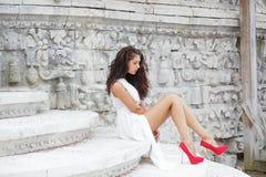 Stående av en ung härlig brunett i en lång vit klänning arkivfoton