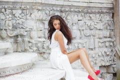 Stående av en ung härlig brunett i en lång vit klänning arkivbild