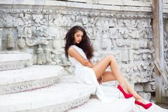 Stående av en ung härlig brunett i en lång vit klänning royaltyfri fotografi