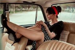 Stående av en ung härlig flicka i en tappningklänning i en retro bil royaltyfri foto