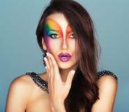 Stående av en ung härlig flicka med en ljus multico för mode royaltyfria bilder