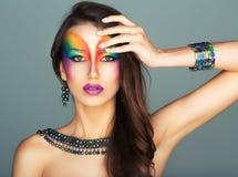 Stående av en ung härlig flicka med en ljus multico för mode arkivbilder