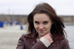 Stående av en ung härlig flicka med långt brunt hår En molnig höstdag på stranden Arkivfoton