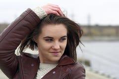 Stående av en ung härlig flicka med långt brunt hår En molnig höstdag på stranden Arkivfoto