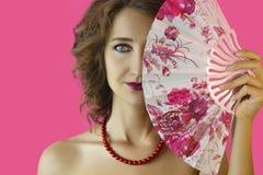 Stående av en ung härlig flicka med ljust smink och en fan i handnärbild på en rosa bakgrund Royaltyfria Bilder