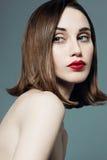 Stående av en ung härlig flicka med röd läppstift i studion på en grå bakgrund Arkivbilder